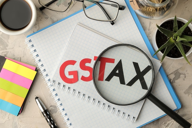 The word gst tax with a notebook, glasses, pen and coins in a can on a light concrete background. view from above