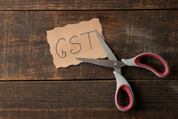Word gst with scissors on a brown wooden background. view from above