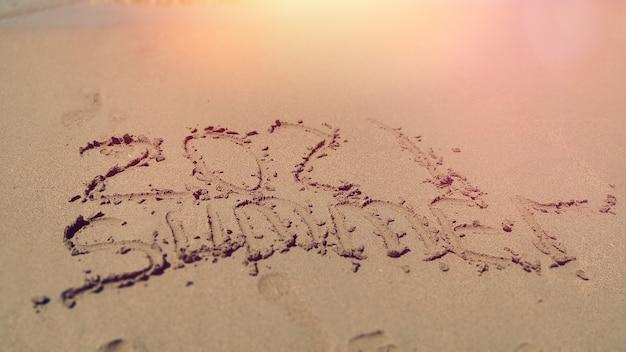 黄色い砂浜で2021年夏の手書きの言葉。ホリデー