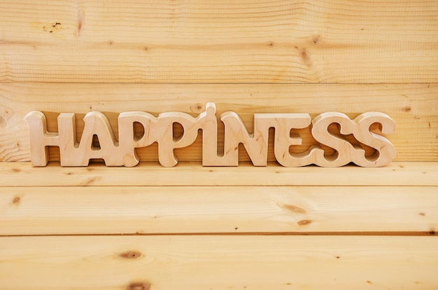 Word happiness carved from  wood on wood background
