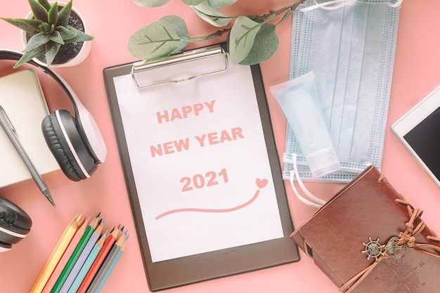 Word happy new year 2021 on clipboard with stationery, mask and hand sanitizer. concept to present new normal lifestyle activities past covid-19 pandemic.
