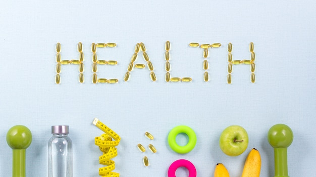 The word health is written with omega 3 capsules surrounded by sports equipment,