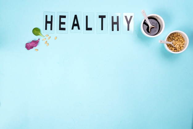The word healthy is laid out on a blue insulated background with two bowls