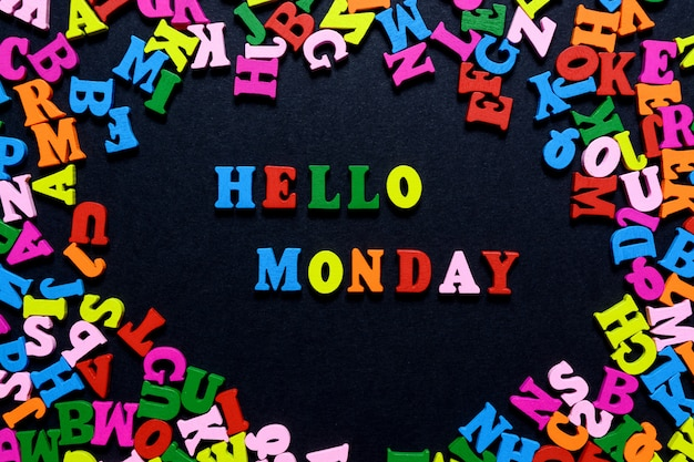The word hello monday from multi-colored wooden letters on a black background