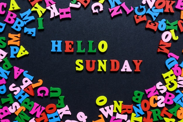 The word hello on sunday from multi-colored wooden letters on a black background