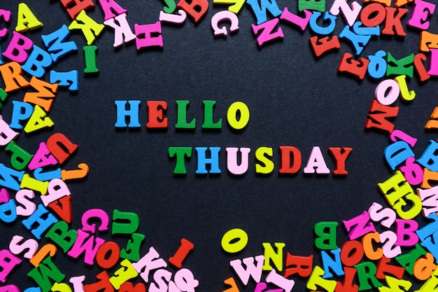 The word hello thusday from multi-colored wooden letters on a black background