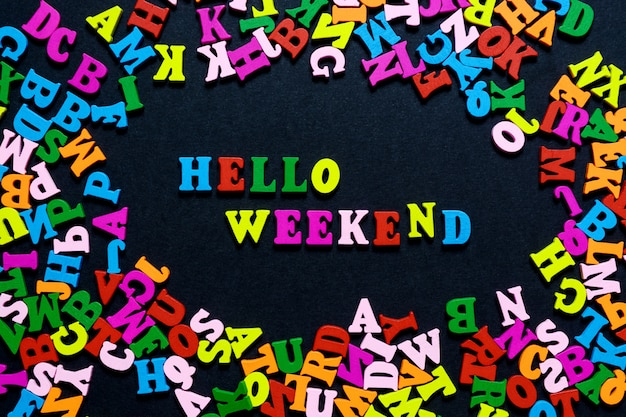 The word hello weekend from multi-colored wooden letters on a black background