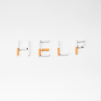 Word help text made from broken cigarette on white background