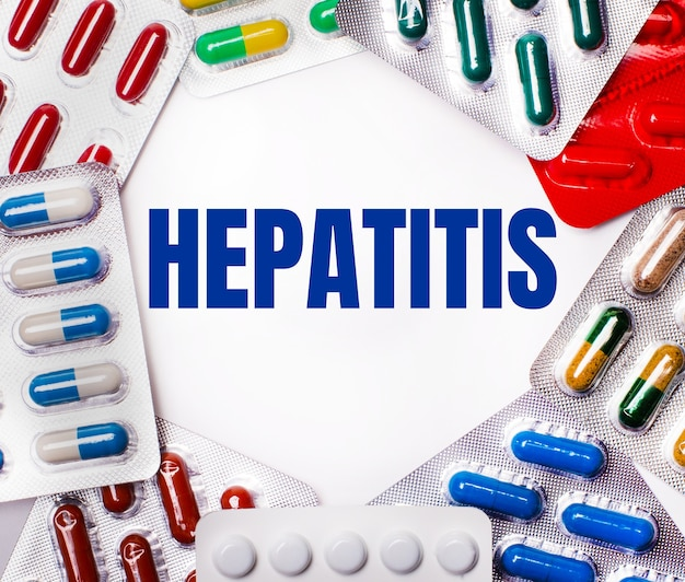 The word hepatitis is written on a light surface surrounded by multicolored packages with pills. medical concept