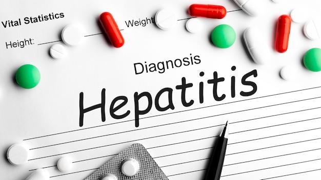 ペン、各種医薬品の丸薬、錠剤、カプセルを含む紙に肝炎という言葉を書く