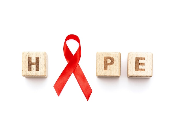 Word hope and red ribbon isolated on white