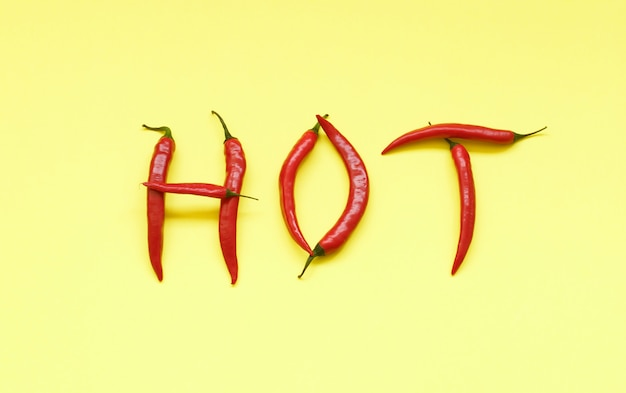Word hot in capital letters filled with red hot chili peppers on yellow