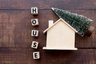 Word house blocks with wooden house and christmas tree on table