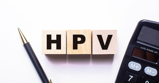 The word hpv is written on wooden cubes between a pen and a calculator on a light surface
