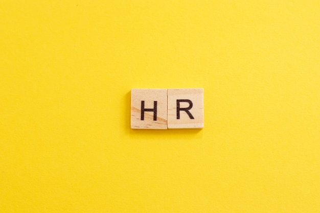 Word hr made from wooden letters on yellow background. human resources. hr concept. new employee