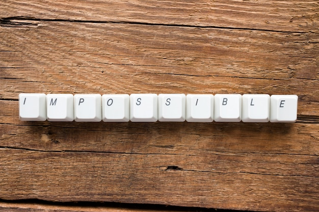The word impossible of keyboard keys on wooden background