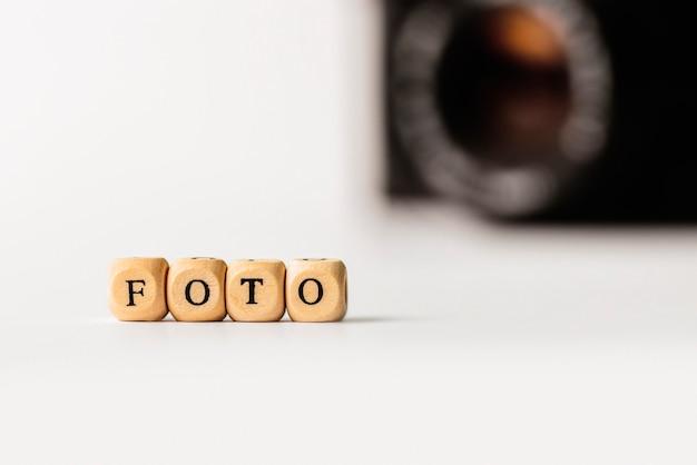 白の写真カメラと木製の文字で単語