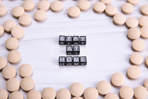 Wordの碑文は、医療薬とフレームの木製のテーブルに家にいます。コロナウイルス、covid-19クローズアップ。上面図
