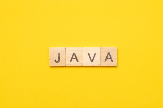 노란색 배경에 나무 글자로 만든 단어 자바. 소프트웨어 개발을위한 최신 프로그래밍 언어.