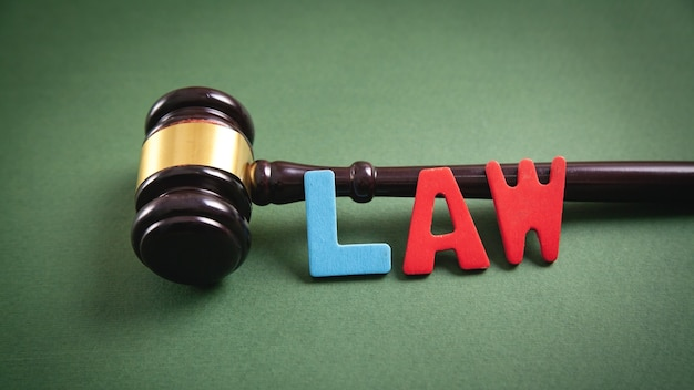 Word law and judge gavel on green background.