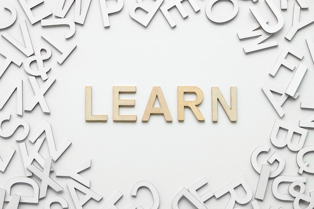 単語は、白い背景の上の木製アルファベットの概念を学びます。