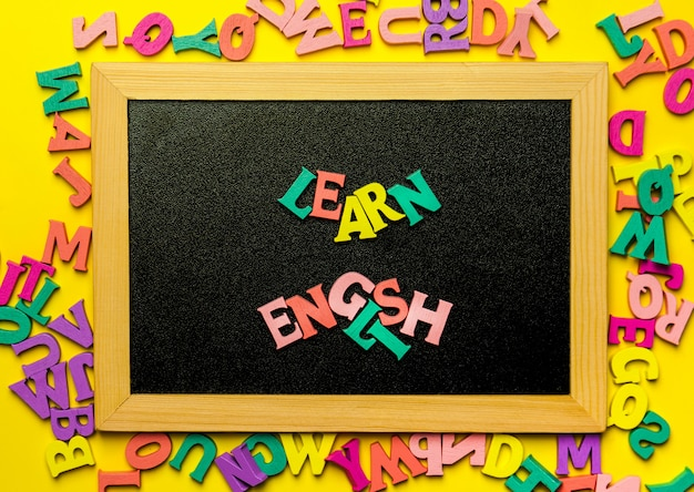 Word learning english made with wooden letters over the wooden board