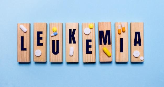 白血病という言葉は、丸薬の近くの水色のテーブルの上の木製のブロックに書かれています