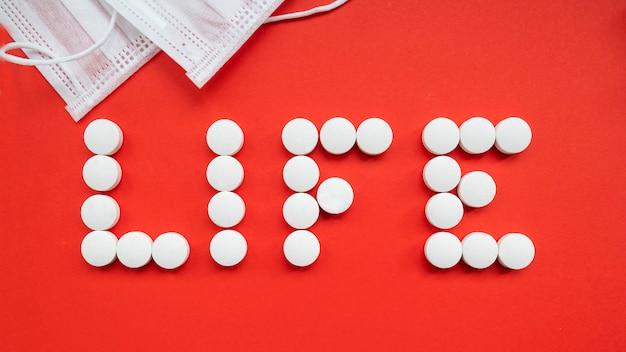 赤い背景の上の白い錠剤から成っている単語の生活。上面図。コロナウイルスを止める