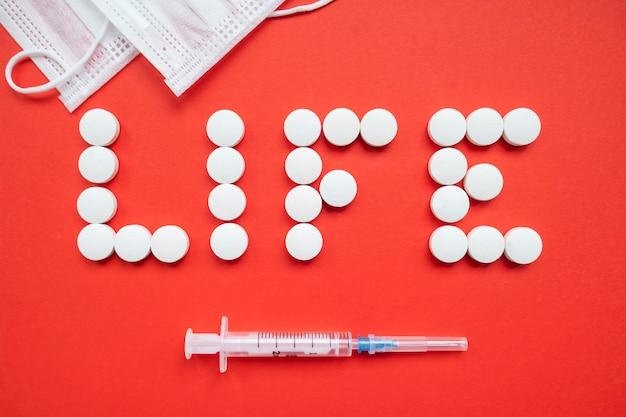 赤い背景の上の注射器と防護マスクと白い錠剤から成っている単語の生活。上面図。コロナウイルスを止める