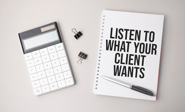 The word listen to what your client wants is written on a white surface next to a pen, calculator and reports