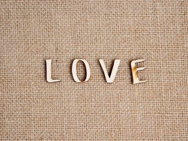 Word love on burlap top view