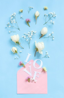 Word love, flowers and pink envelope on a light blue background top view
