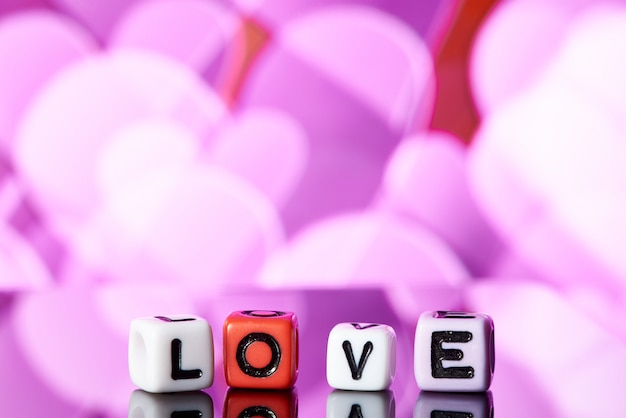 Word love  from cubes with reflection on bright blurred background.