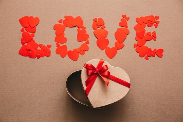 Слово любовь из сердечек и открытая подарочная коробка в форме сердца