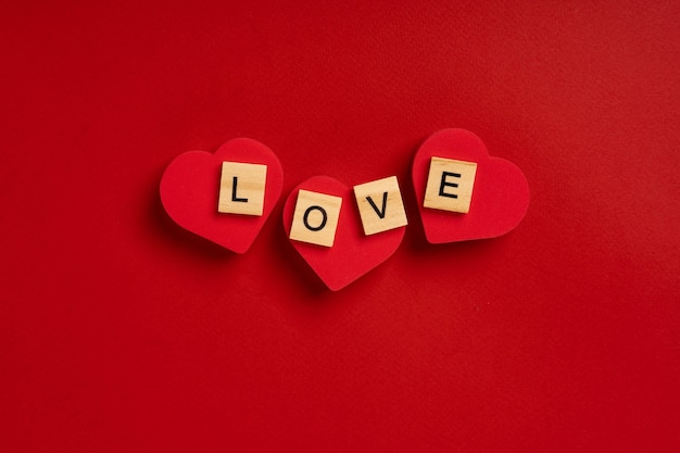 The word love from wooden blocks lies on hearts on a red background