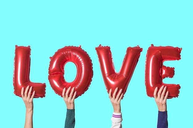 明るい背景の手に赤い風船から英語のアルファベットの単語の愛