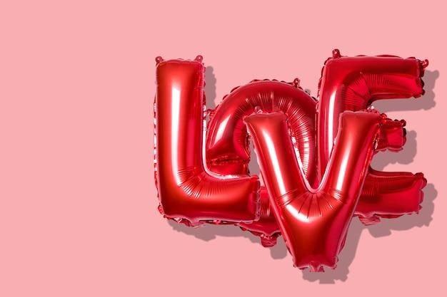 明るい背景の上の赤い風船から英語のアルファベットの単語の愛