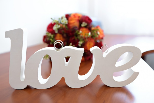 Word love inscription costs on a table with rings
