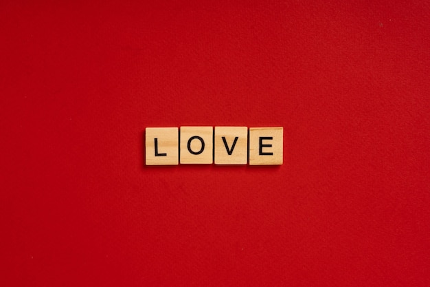 The word love is made of wooden blocks on a red background