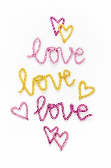 The word love is written out with pink and gold tinsel. love and heart symbols. flat lay, top view
