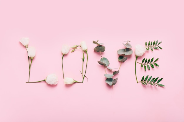 Word love made of flowers and leaves on pink.