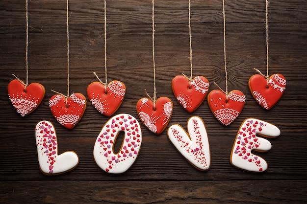 나무 테이블에 밧줄에서 매달려 하트 모양의 쿠키와 쿠키로 만든 단어