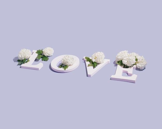 白い文字と美しい白い花で作られた言葉の愛。春の恋人たちのメッセージ。最小限の自然の概念。