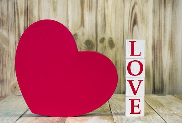 木製の立方体のブロックと木の板に大きな赤いハートで作られたwordlove。バレンタインデーやコピースペース付きのロマンチックなイベントのグリーティングカード。結婚式の招待状またははがき。