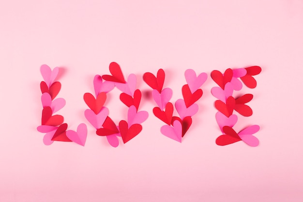 Word love made of paper hearts on a pink background.