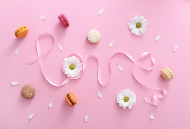 Word love made of pink ribbon with macaroons, white flowers and petals
