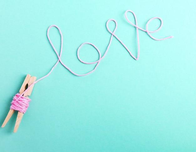 ピンクのウールのロールで作られた愛という言葉