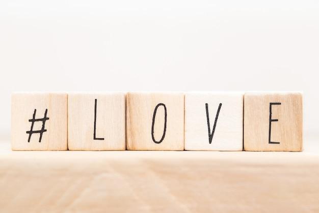 Слово любовь на деревянных кубиках с хэштегом, крупным планом возле белого фона валентина концепции