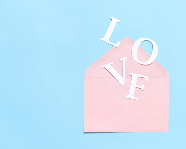Word love and pink envelope on a light blue background top view