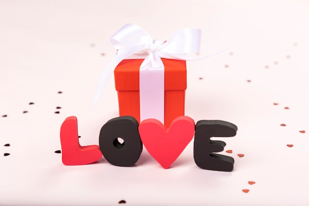 Word love and red gift box on white surface